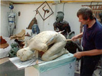 Len works without Hannah, smoothing down the clay in preparation to adding the arms.